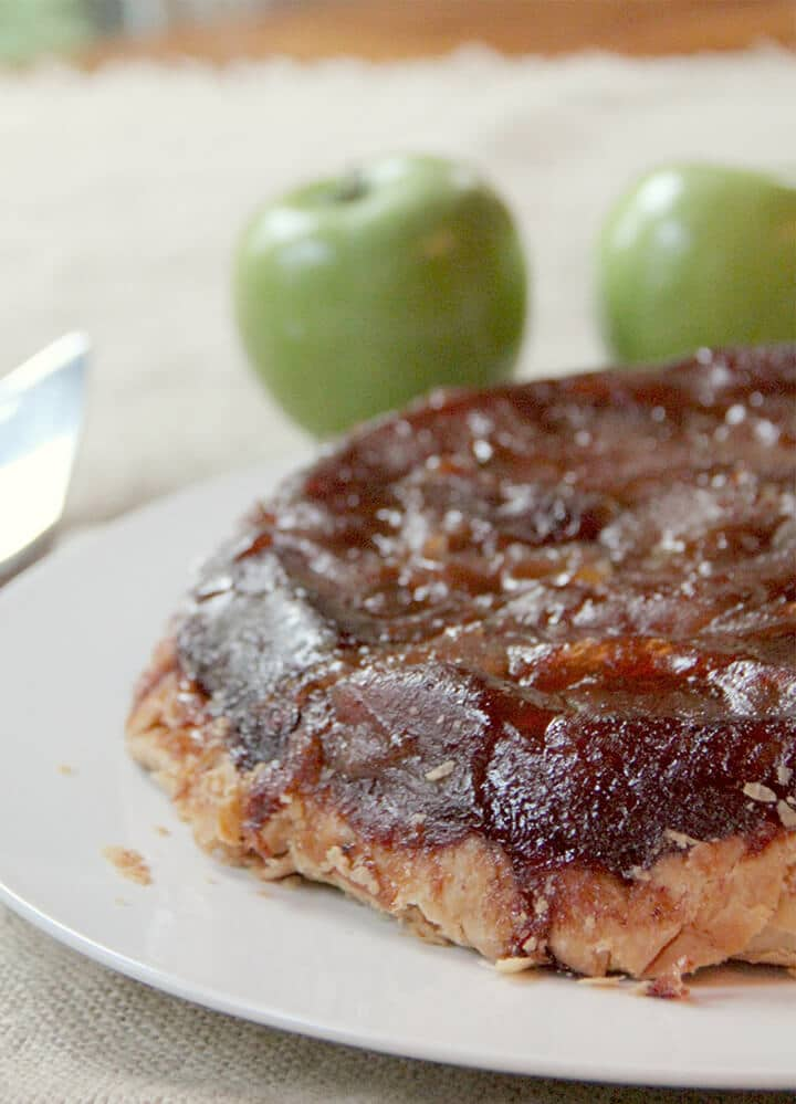 Side view of apple tarte tatin recipe with apples in the background.