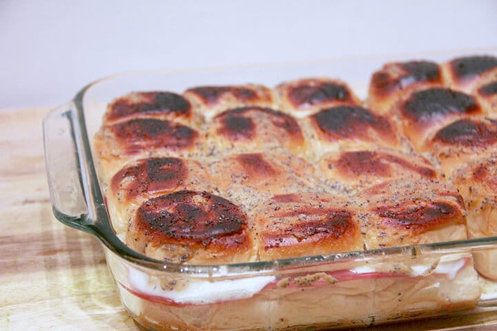 A dish of baked italian sliders with cheese.