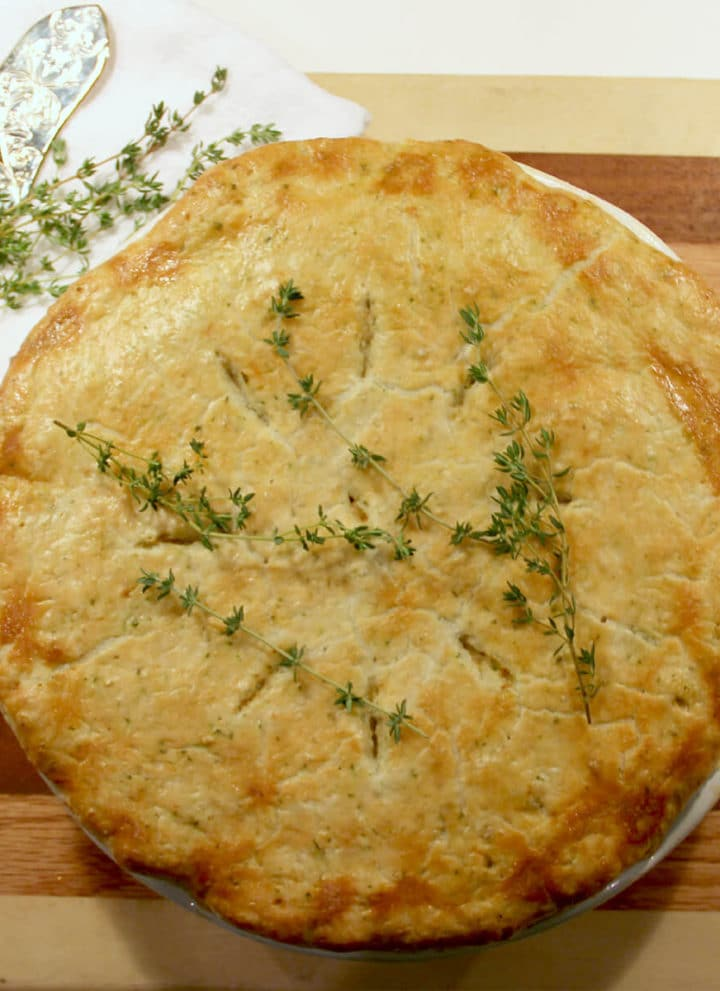Overhead photo of a whole double crust chicken pot pie on a wooden board.