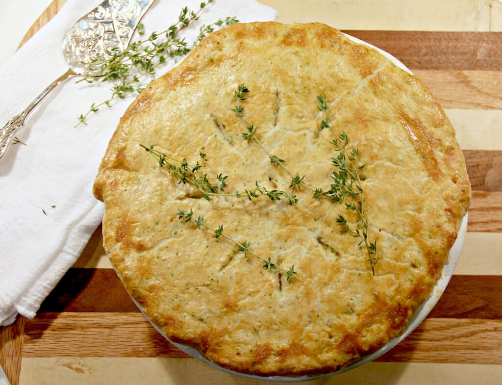 A whole double crust chicken pot pie topped with sprigs of fresh thyme on a cutting board.