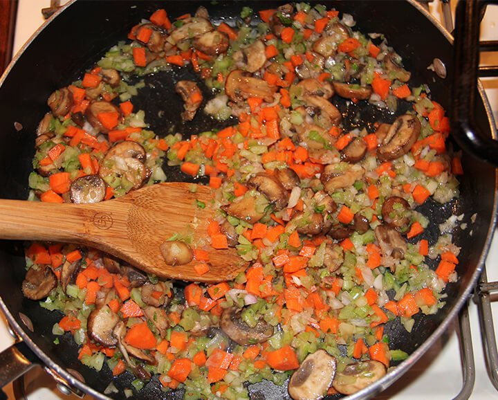 Stirring carrots, celery, onions, and mushrooms with a wooden spoon in a skillet.