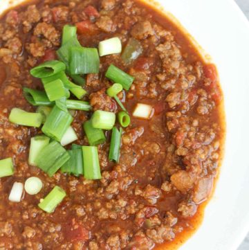 A bowl of chili without beans on the grey counter.