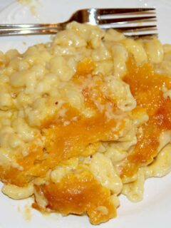 A serving of creamy baked macaroni and cheese on a white plate.