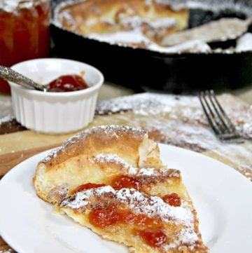 A white plate on a cutting board with a slice of Dutch Baby German Pancake.