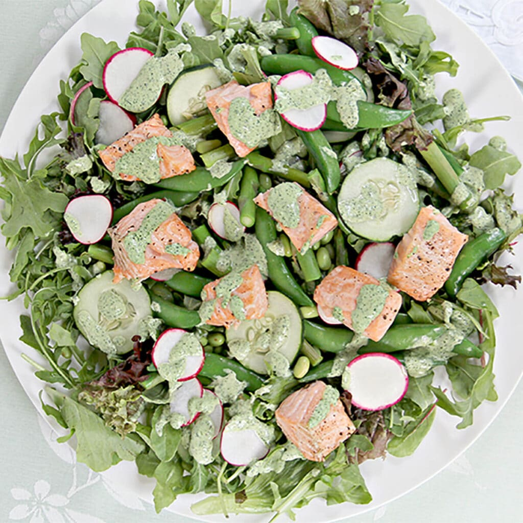 Overhead shot of spring salad with asparagus, sugar snap peas, cucumbers, salmon on a white plate.