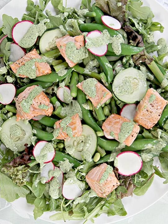 Closeup of spring salad with baked salmon and fresh spring vegetables on a white platter.
