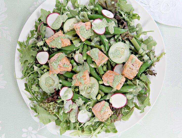 Baked salmon on top of greens with fresh spring vegetables on a white plate.