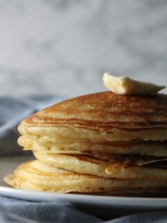 A stack of buttermilk pancakes on a plate over a blue napkin.