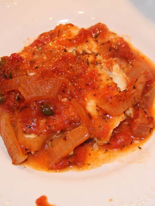 A white plate with Mediterranean fish with tomatoes, onions, and capers.