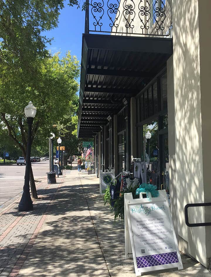 View of a street with shops and street lamps in downtown Aiken, SC.