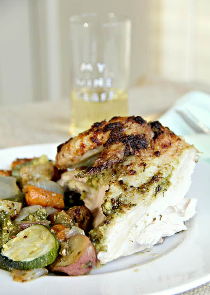 A white plate with chicken and vegetables on it and a small glass of wine in background.