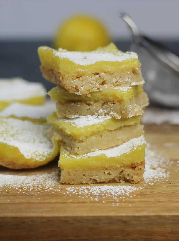 A stack of easy lemon bars sprinkled with powdered sugar on a cutting board.