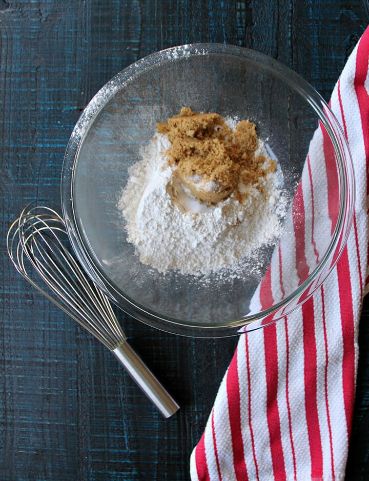 Flour and brown sugar in a glass bowl with a wire whisk and a red striped towel on a cutting board.