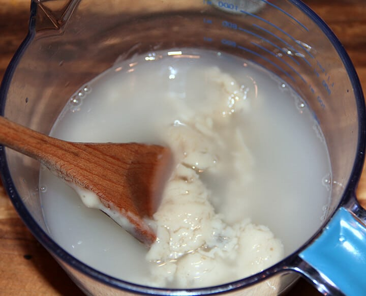 A glass mixing bowl with cream of mushroom soup and water stirred with a wooden spoon.