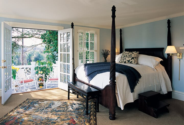 A four-poster bed with white coverlet and porch in the Churchill Suite at The Willcox Hotel.