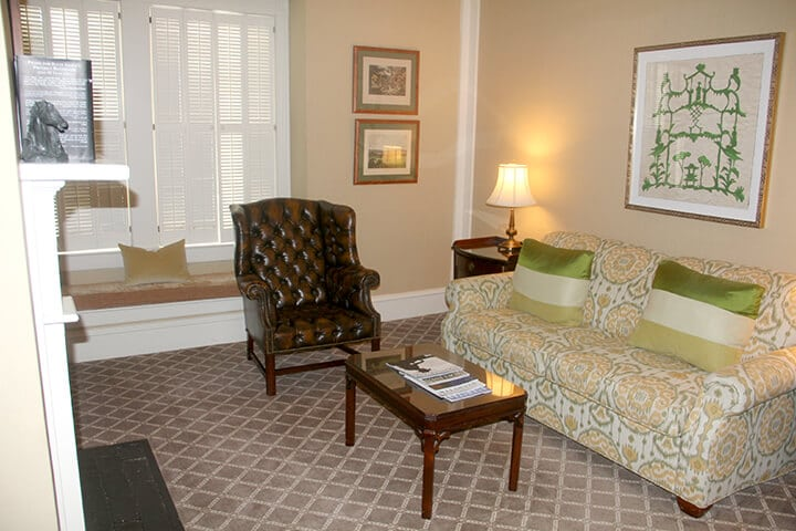 Sitting room with a green patterned sofa and brown chair in the suite at The Willcox Hotel.
