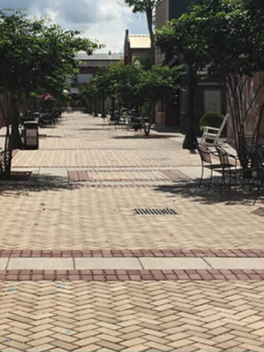 A brick-lined alley with tables and chairs in downtown Aiken, SC.