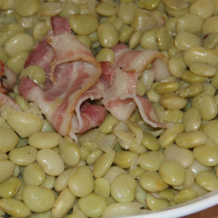 A white bowl filled with cooked butter beans and bacon.