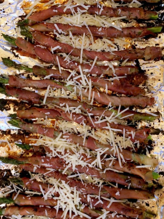 Prosciutto wrapped asparagus crispy from the grill and sprinkled with Parmesan cheese is one of our favorite and easiest appetizers!