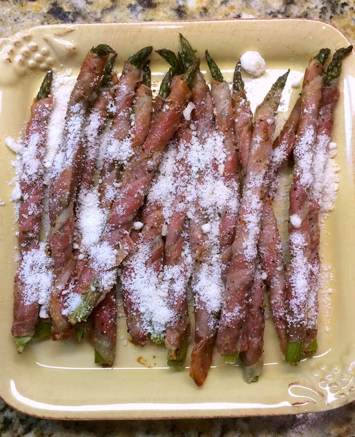 A yellow plate with prosciutto wrapped asparagus spears.