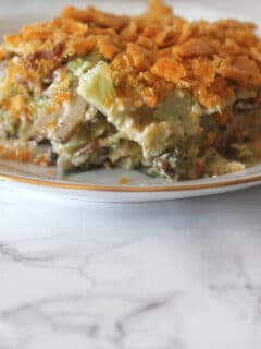 A closeup of a serving of Southern Broccoli Casserole on a plate over a marble board.