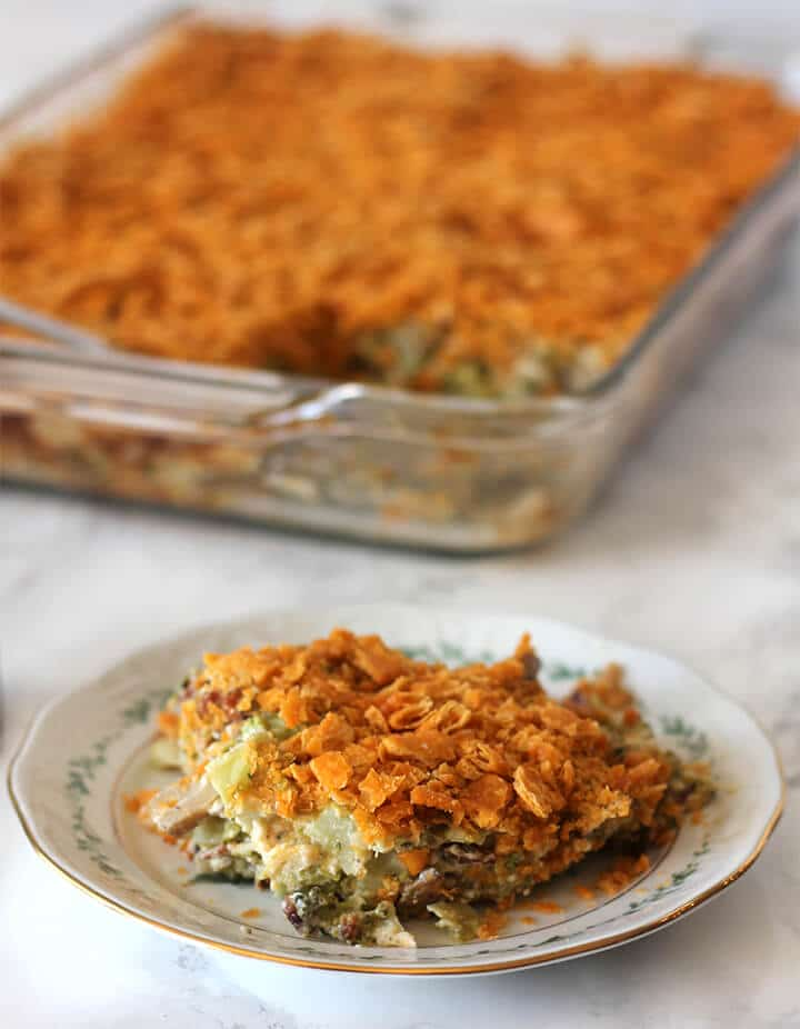 A serving of Southern broccoli casserole on a plate with the casserole dish in the background.