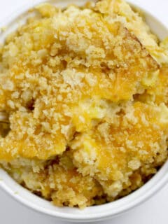 A white dish filled with squash casserole with crumbled Ritz crackers.