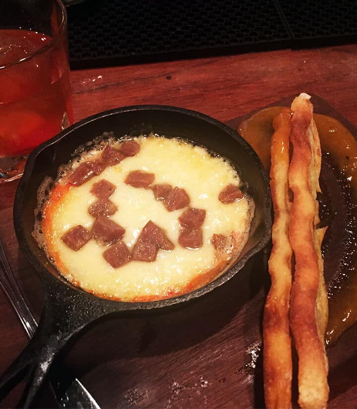 Melted cheese and ham in a small skillet with two breadsticks.