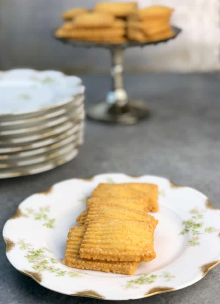 Cheese straws on a plate with a platter of more in the background.