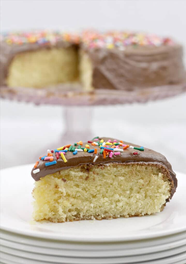 A slice of one layer cake with chocolate frosting and sprinkles on white plates.