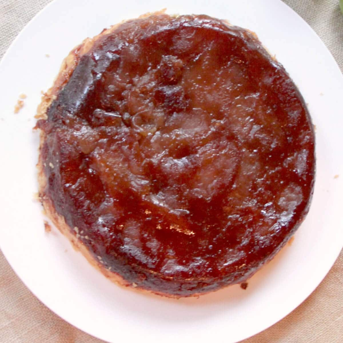 A whole apple tarte tatin on a white plate.