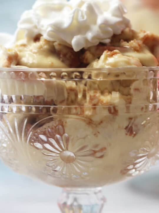 A clear glass bowl of banana pudding topped with whipped cream.