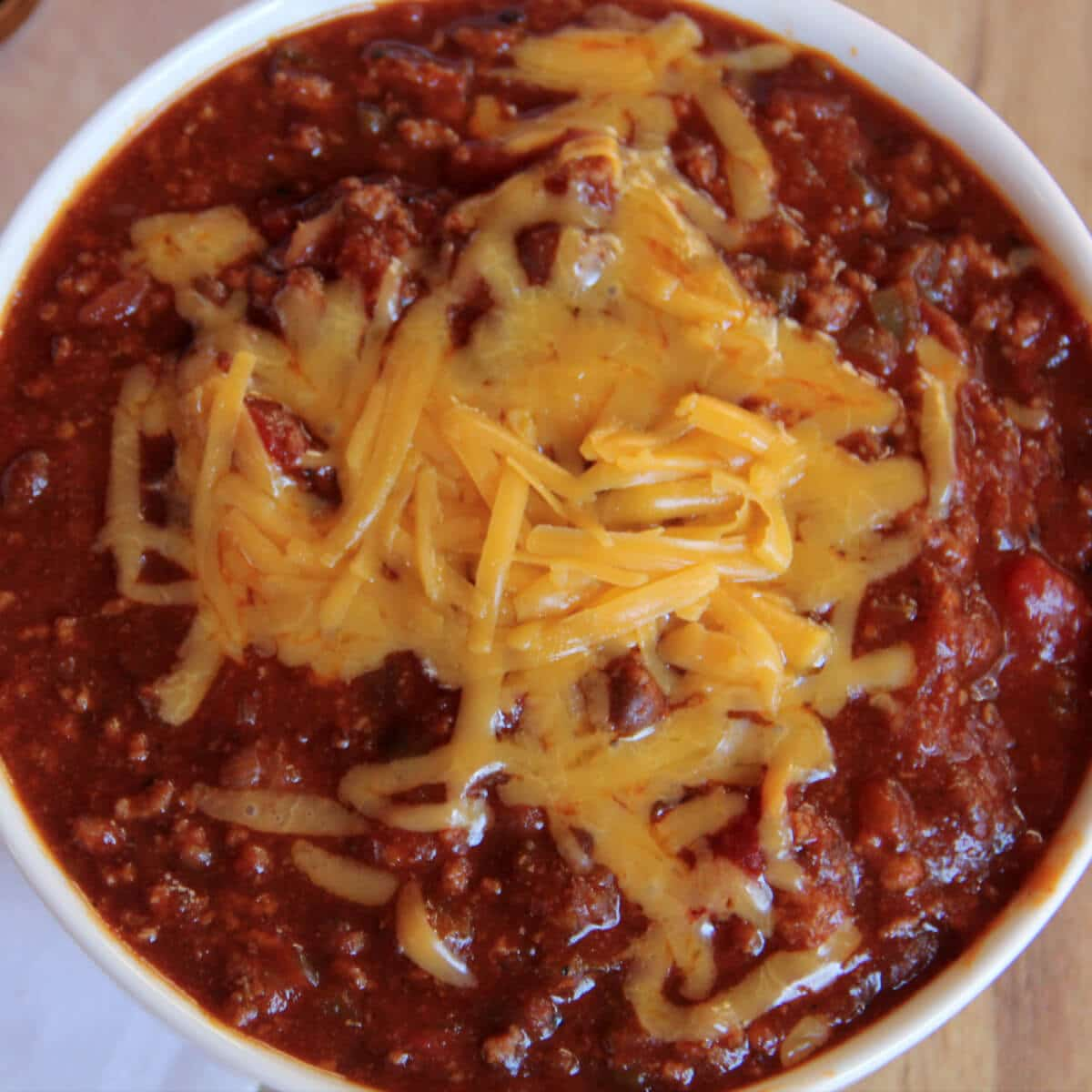 A white bowl of classic beef chili topped with grated cheese.