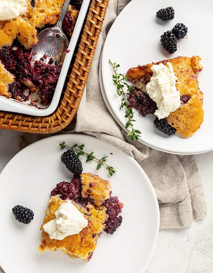 Two white plates with servings of blackberry cobbler with whipped cream.
