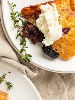 A serving of blackberry cobbler with whipped cream on a white plate.