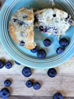 A blueberry muffin on a blue plate on a cutting board with blueberries.