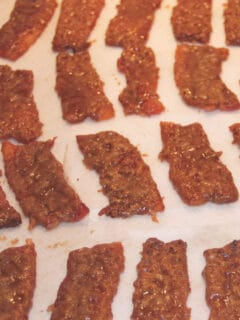 Pieces of caramelized bacon on a platter lined with parchment.