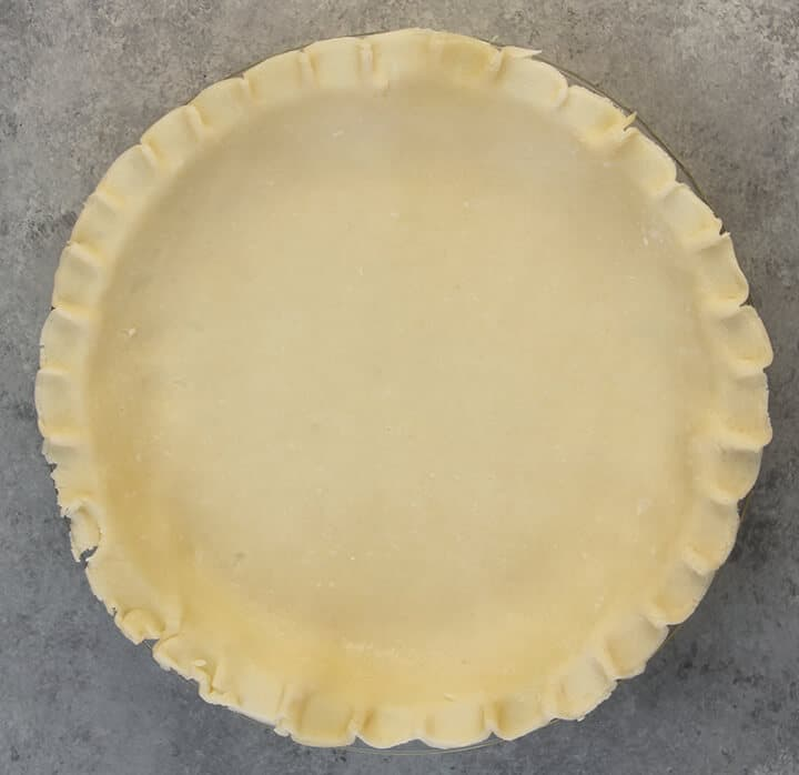 Pie crust in a dish on a grey counter.