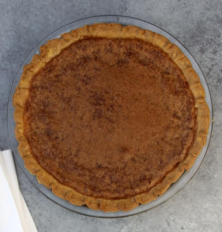Overhead photo of a baked chess pie on a grey counter.