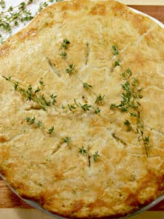 Double crust chicken pot pie on a cutting board with fresh thyme.