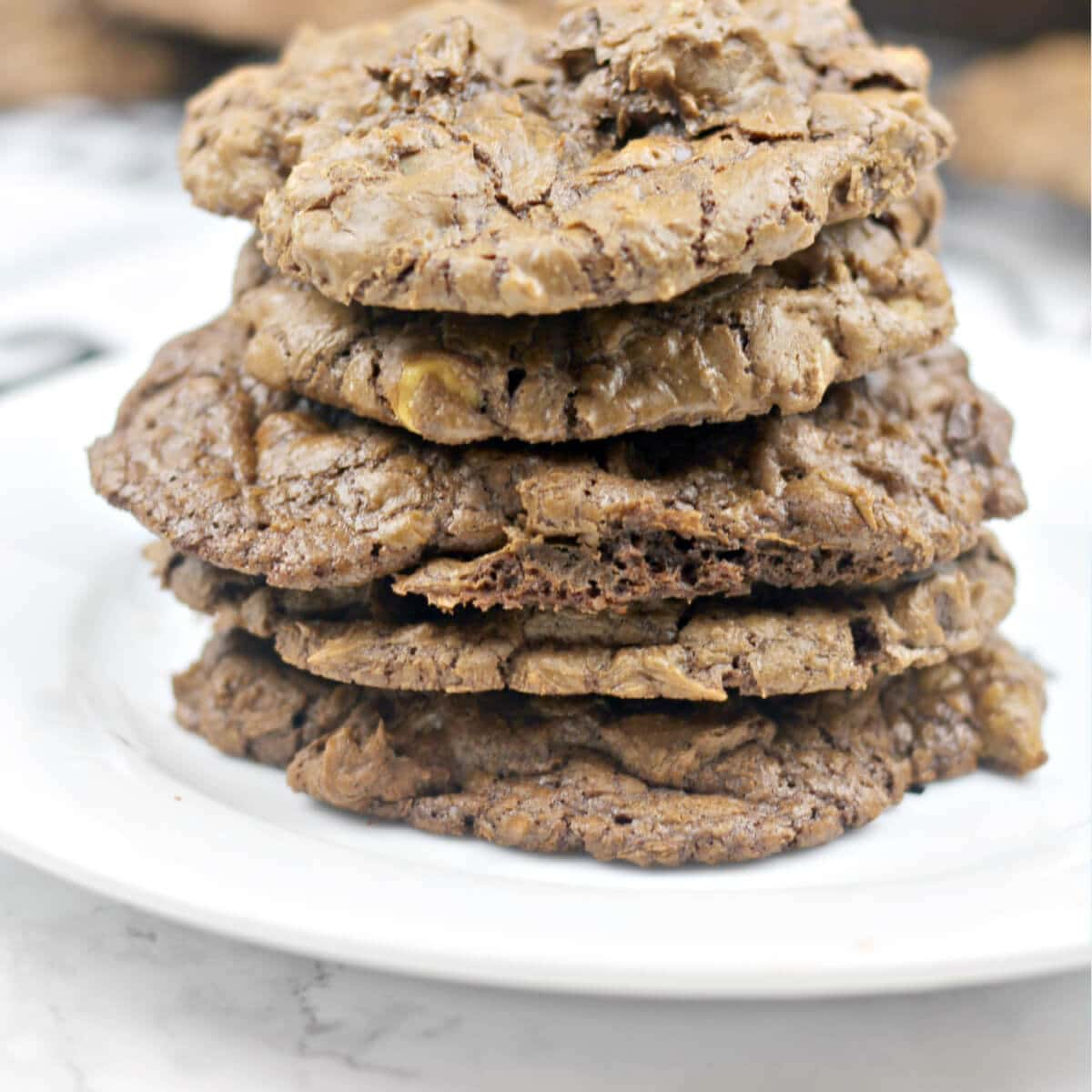 Chocolate and peanut butter cookies stacked on a white plate.