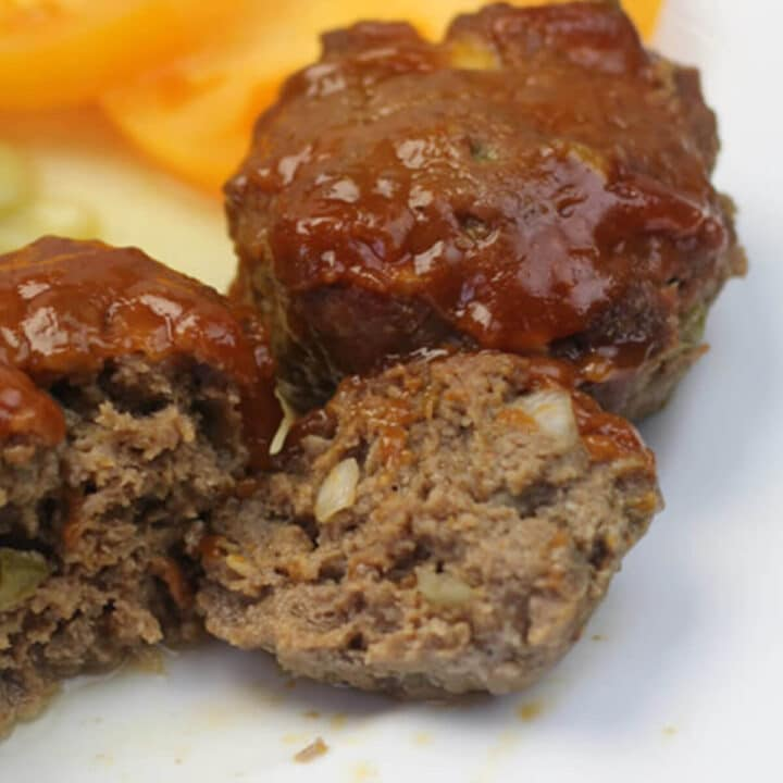 A white plate with three meatloaf muffins covered in ketchup sauce.