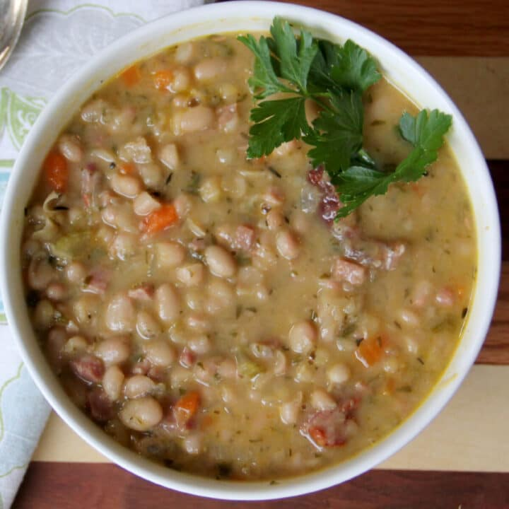 A white bowl filled with navy bean and ham soup with a sprig of parsley.