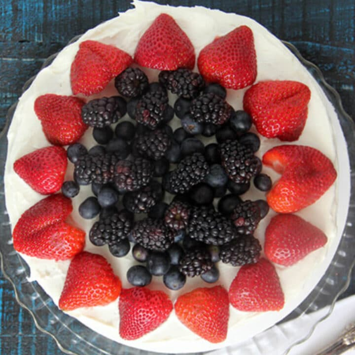 Red white and blue cake with strawberries and blueberries on a blue background.