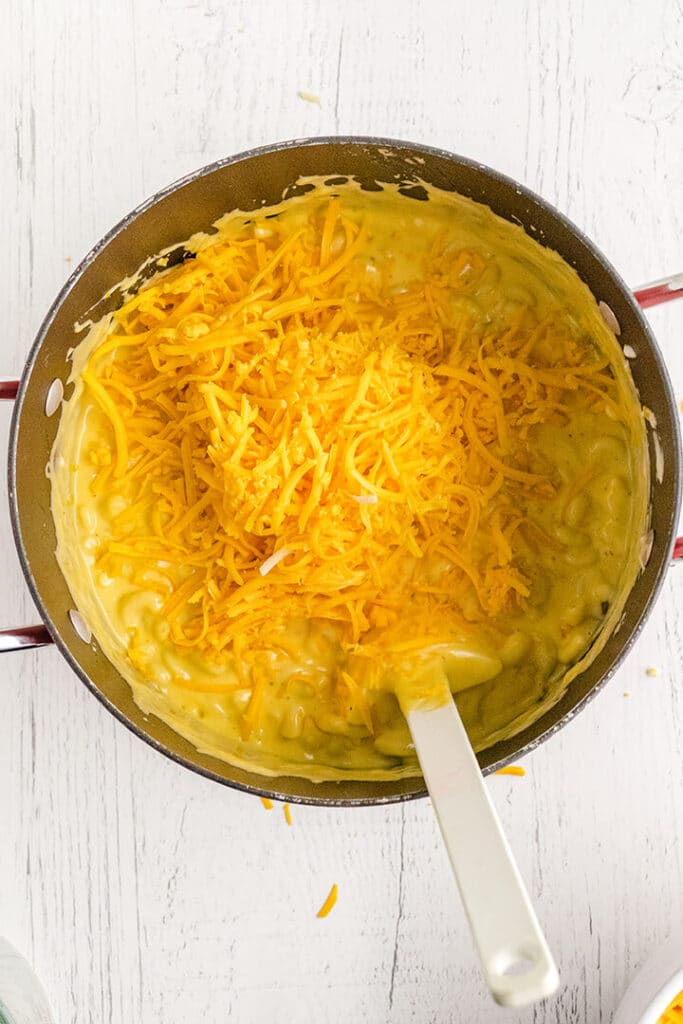 A pot with noodles and grated cheese with a white spoon for mac and cheese.