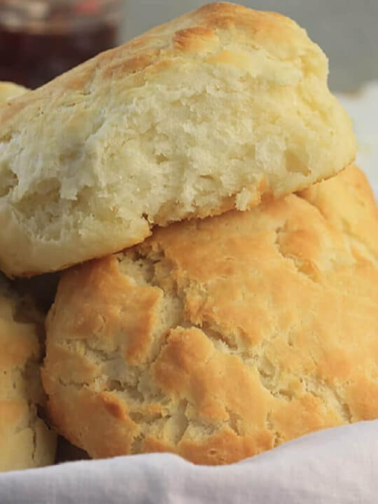 Closeup of buttermilk biscuits in a basket with a white towel.