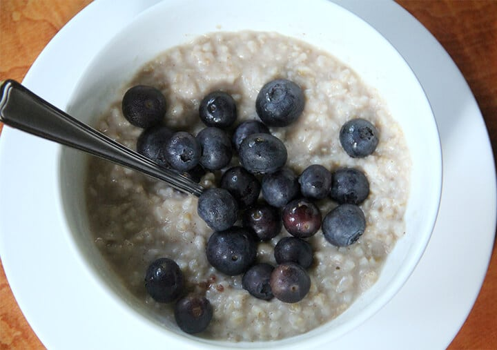 A white bowl filled with Brown sugar oatmeal topped with blueberries.