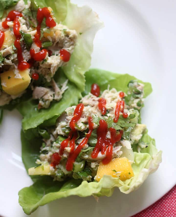 Closeup of chicken lettuce wraps on a white plate with a drizzle of Sriracha sauce.