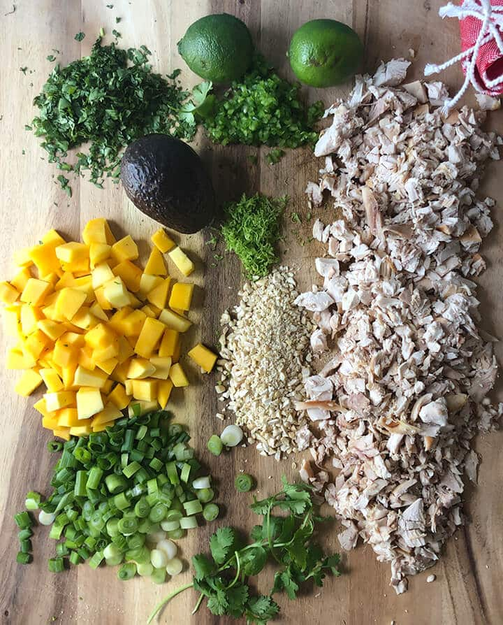 Chicken, cilantro, and other ingredients on a cutting board for chicken lettuce wraps.