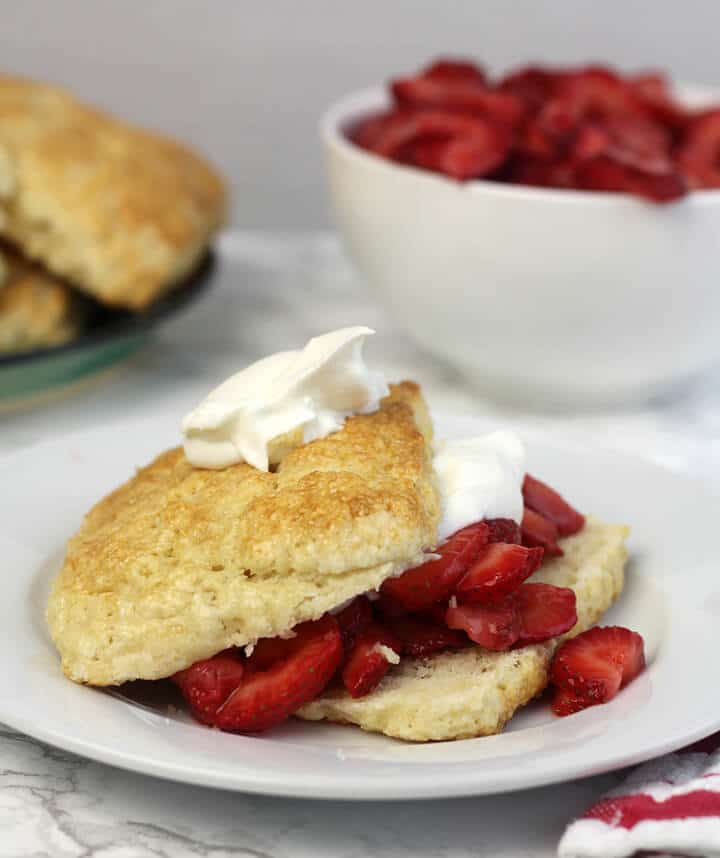 Strawberry shortcake on a white plate with a bowl of strawberries in the background.